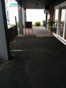 Der Boden vor dem Restaurant ist mit Gummimatten ausgekleidet. Er wirkt dadurch nicht so kalt, die schwarze Farbe signalisiert Eleganz, Zeitlosigkeit und Klasse