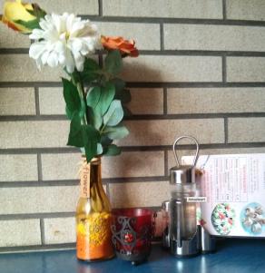 """Dieses Ensemble aus Grablicht, """"Flower""""-etikettiertem Kunstblumenbouquet in gelbgefärbter, mit Dekosteinen und –sand gefüllter Flasche und Tafelessig einfach mal einen Augenblick wirken lassen"""